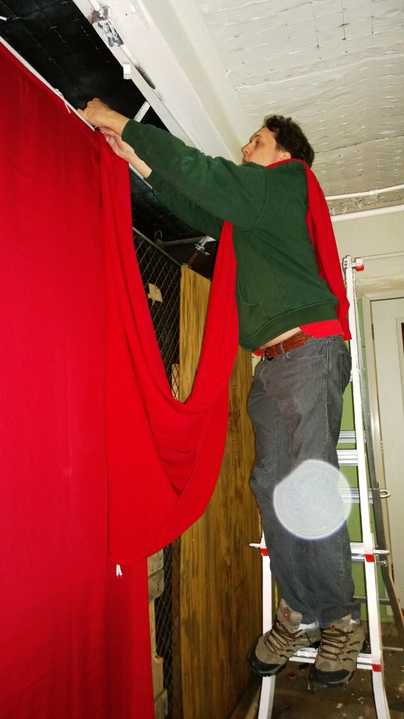 Kevin hangs curtains.