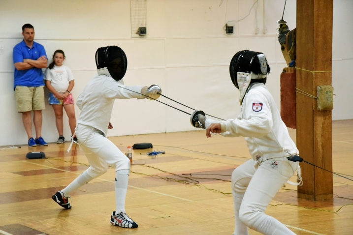 Kaden attempts to hit his opponent on the arm in Y12 Epee.